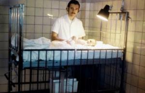 """Figura 1- Eduardo Cueto Rua cuidando de uma criança colocada em """"Balance"""" (Balanço Metabólico), notar embaixo da cama a proveta volumétrica que era utilizada para mensurar as perdas fecais separadas de urina. Cueto era um dos especializandos de La Plata de quem tornei-me íntimo amigo, amizade que perdura inabalável até os dias atuais. Cueto trabalha no Hospital Soror Ludovica em La Plata aonde é chefe do Serviço de Gastroenterologia; ele tem especial interesse pela Doença Celíaca."""