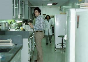 Figura 27- Eu em plena atividade de preparo do material para visualização no microscópio eletrônico. Ao fundo vê-se a técnica Hyacinth Spencer uma jamaicana, pessoa admirável e de espírito altamente divertido, que também trabalhava no laboratório.