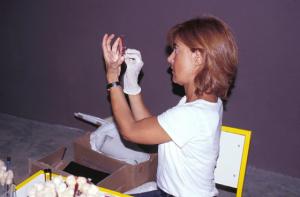 Figura 26- Profa. Isabel em seu trabalho de semeadura imediata, nas placas de Petri, das amostras de fezes por mim coletadas.