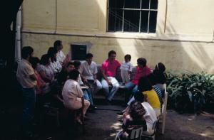 Figura 8- Foto das tradicionais reuniões com os residentes para discutir os casos dos pacientes internados no pátio central do Serviço de Pediatria, no início da década de 1990. Estou sentado no banco de pedra ladeado à esquerda por Dr. Jairo Cesar dos Reis e à minha direita Dr. Carlos Alberto Garcia Oliva.
